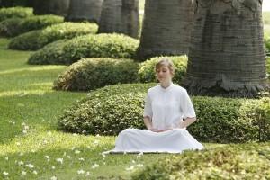 mulher vestida de branco sentada em um gramado meditando