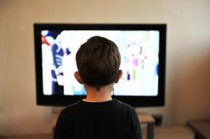 menino sentado vendo televisão