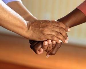 duas pessoas que se dão aos mãos em uma atitude de compreensão