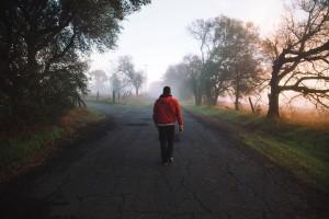 homem sozinho caminhando na rua com neblina