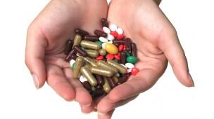 mãos que seguram diversas cápsulas de remédio em diferentes tamanhos e cores