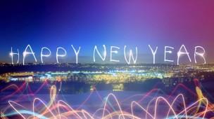 paisagem de uma cidade com céu em tons de azul claro e escuro. Escrito feliz ano novo em inglês, com luzes neon em diversas cores na frente