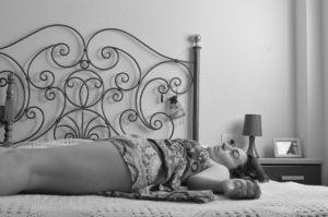 foto em preto e branco mostra um quarto com uma mulher jogada sobre a cama que parece triste