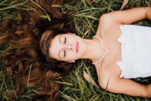 mulher deitada sobre a grama com vestido branco e um colar de pérolas no pescoço. Com um rosto de aspecto feliz e sonhador.
