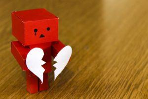 boneco feito de papelão na cor vermelha, com aspecto triste segurando um coração partido de papel branco.