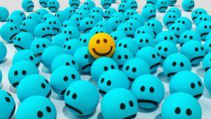 várias bolinhas na cor azul com uma carinha triste e uma única bolinha na cor amarela com uma carinha feliz.
