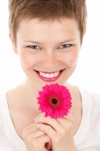 moça sorrindo com uma flor rosa na mão