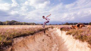 rapaz que pula uma vala de um terreno junto com um cachorro