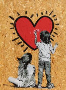mural desenhado um coração e uma menina sentada com um menino que desenha no coração