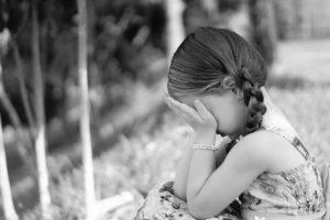 criança menina triste sentada no chão com as mãos nos olhos