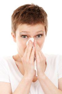 mulher gripada assoando o nariz com um lenço