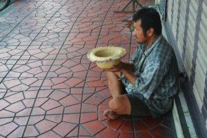 homem sentado pedindo esmolas