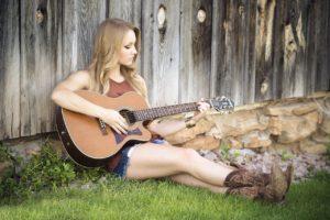 moça sentada tocando um violão