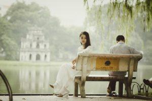 mulher e homem que estão brigados sentados em um banco próximo a um lago