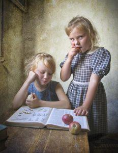 meninas crianças comendo maçãs e estudando um livro.