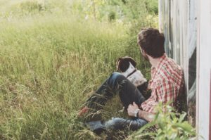 rapaz sentado com seu cachorro ao lado em uma área rural.
