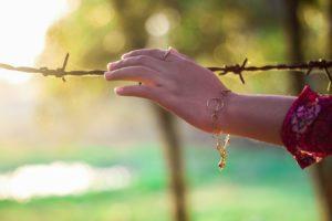 mulher que coloca a mão sobre uma cerca de arame farpado