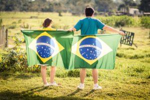 dois jovens que seguram a bandeira brasileira