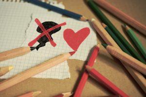 imagem de papeis e lápis colorido, mostra uma nuvem negra com um x encima e um coração ao lado