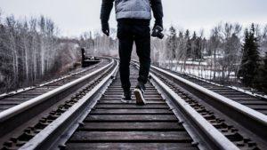 homem que caminha sobre trilho de trem