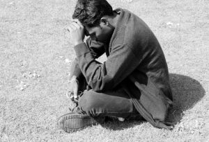 homem triste sentado fazendo uma oração