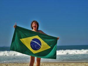 mulher em uma praia segurando a bandeira brasileira