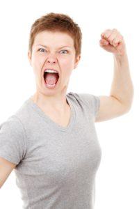 mulher mostra raiva fechando os punhos e tendo uma atitude agressiva