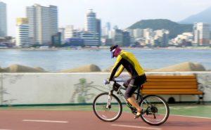 ciclista pedalando em uma ciclovia imagem ao fundo de água e prédios