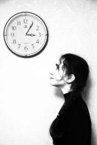 menina que olha para um relógio na parede