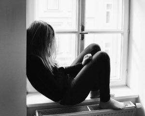 mulher triste sentada em uma janela